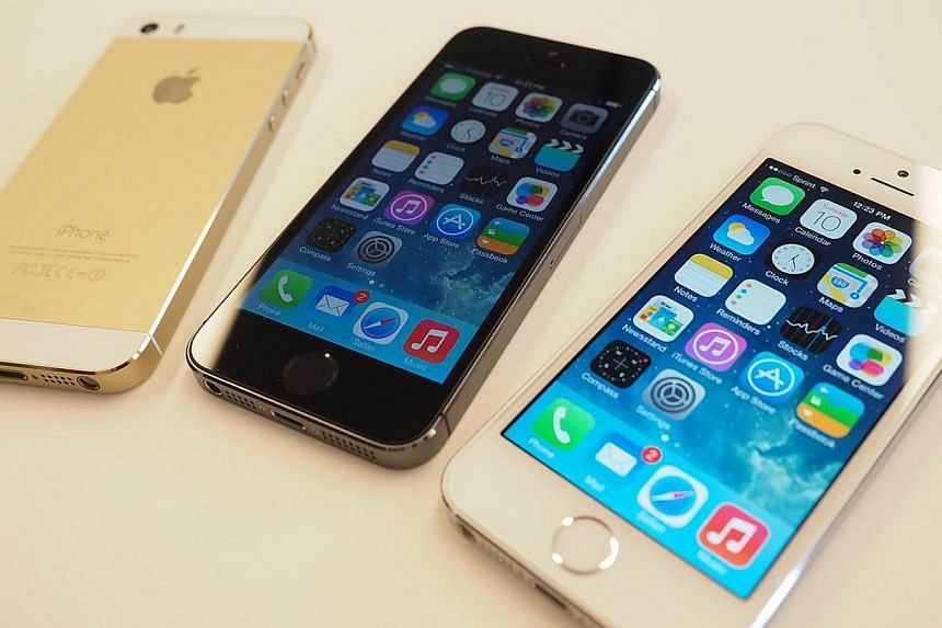 The new iPhone 5S is displayed during an Apple product announcement at the Apple campus. Apple's flagship handset now also comes in a third colour, gold.-- ST PHOTO: TREVOR TAN