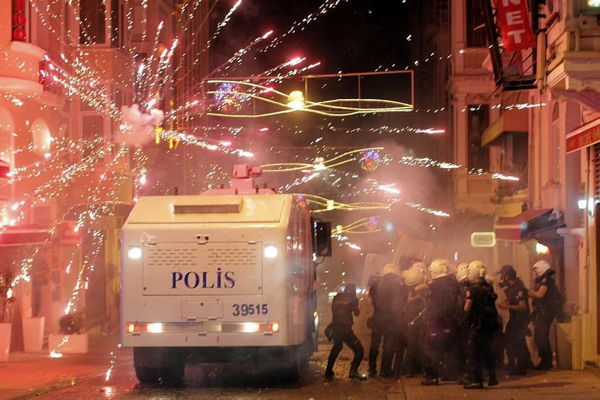 Turkish protesters use fireworks as riot policemen take position during clashes in Istanbul, Turkey, on Tuesday Sept 10, 2013. Turkey's Interior Minister Muammer Guler said on Wednesday that protesters were attempting to use the death of a young