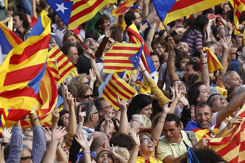 """Catalan separatist flags are waved as a crowd forms a human chain to mark the """"Diada de Catalunya"""" (Catalunya's National Day) in central Barcelona Sept 11, 2013. Hundreds of thousands of Catalans held hands in a 400km human chain across their region"""