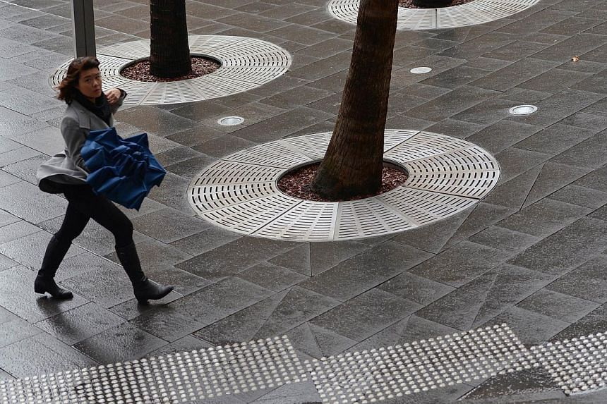 An office worker (left) walks through the central business district in Sydney on Aug 8, 2013. Australia suffered a surprising drop in employment in August that pushed the jobless rate up to a four-year high of 5.8 per cent, a disappointingly soft rep