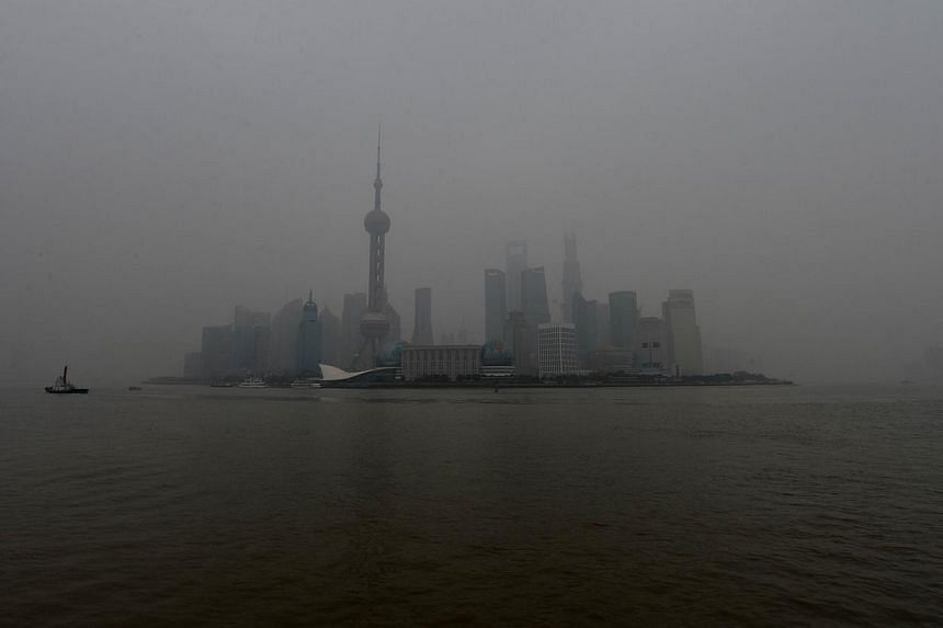 A file photo taken on Jan 16, 2013 shows the Pudong business district shrouded by heavy air pollution in Shanghai. China will aim to cut total coal consumption to below 65 percent of total primary energy use by 2017 as part of a comprehensive new pla
