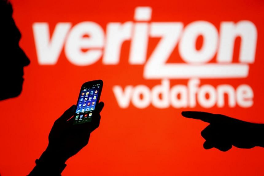 A man is silhouetted against a video screen with Vodafone and Verizon texts as he poses with a Samsung Galaxy S3 in this photo illustration taken in the central Bosnian town of Zenica, Sept 3, 2013. Verizon smashed records with a blockbuster US$49 bi