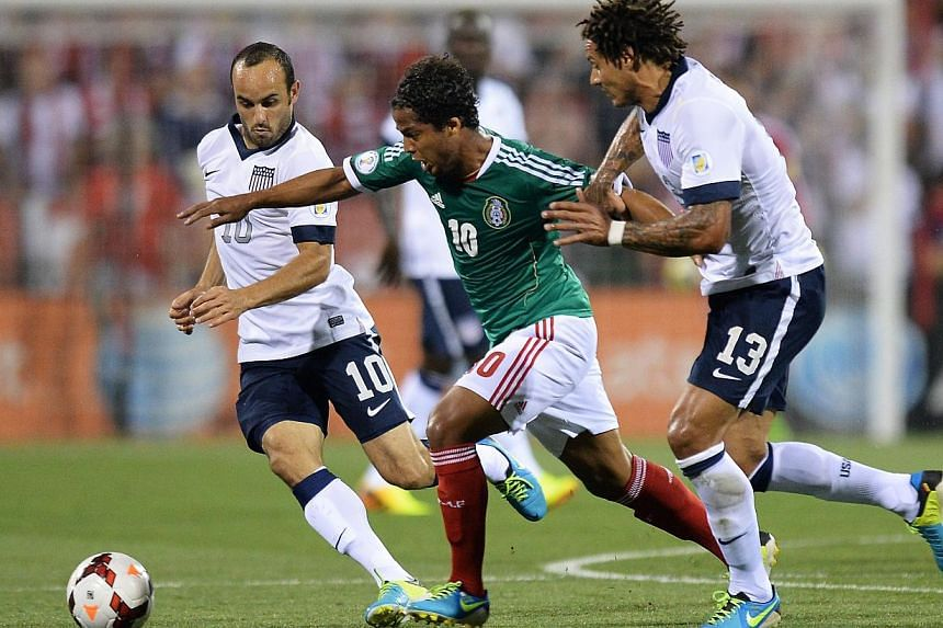 Landon Donovan #10 of the United States Men's National Team and Jermaine Jones #13 of the United States Men's National Team defend against Giovani dos Santos #10 of the Mexico Men's National Team in the first half at Columbus Crew Stadium on Sept 10,