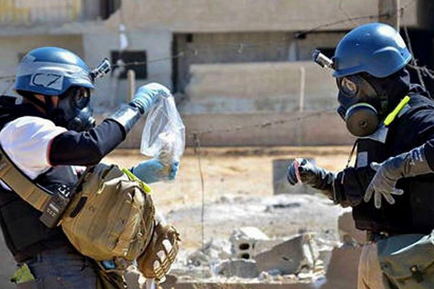 In this Wednesday, Aug 28, 2013 citizen journalism image provided by the United media office of Arbeen which has been authenticated based on its contents and other AP reporting, members of the UN investigation team take samples from sand near a part