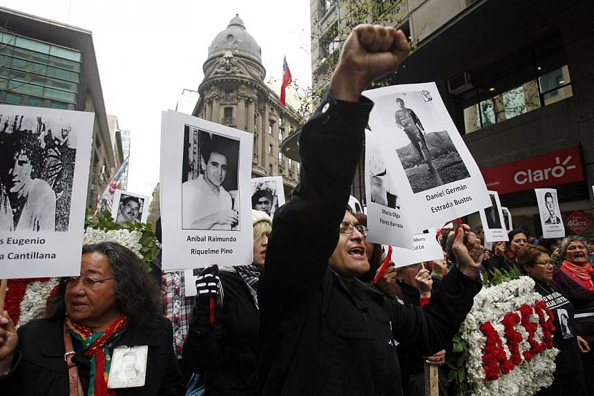 Relatives of victims of Chile's dictatorship march outside La Moneda presidential palace in Santiago, Chile, on Wednesday, Sept 11, 2013.Chile marked the 40th anniversary Wednesday of a coup that brought dictator Augusto Pinochet to power, amid
