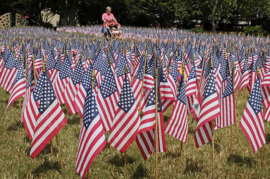 An unidentified woman pushes a toddler as she walks through a sea of flags set up to honor the victims of the Sept. 11 attacks in Matthews, N.C., on Wednesday, Sept 11, 2013. Today marks the 12th anniversary of the terrorist attacks. War-weary Americ