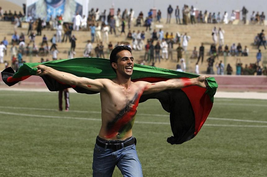 An Afghan football fan runs with the national flag as he celebrates their national football team's victory in the South Asian Football Federation Championship, at the Kabul stadium on Thursday, Sept 12, 2013. President Hamid Karzai embraced Afgh