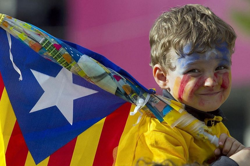 A young boy holding an Independentist Catala flag (Senyera) smiles as Catalans gather in a bid to create a 400km human chain in Barcelona, on Thursday, Sept 11, 2013. See more pictures from around the world in Through The Lens' Today in Pictures