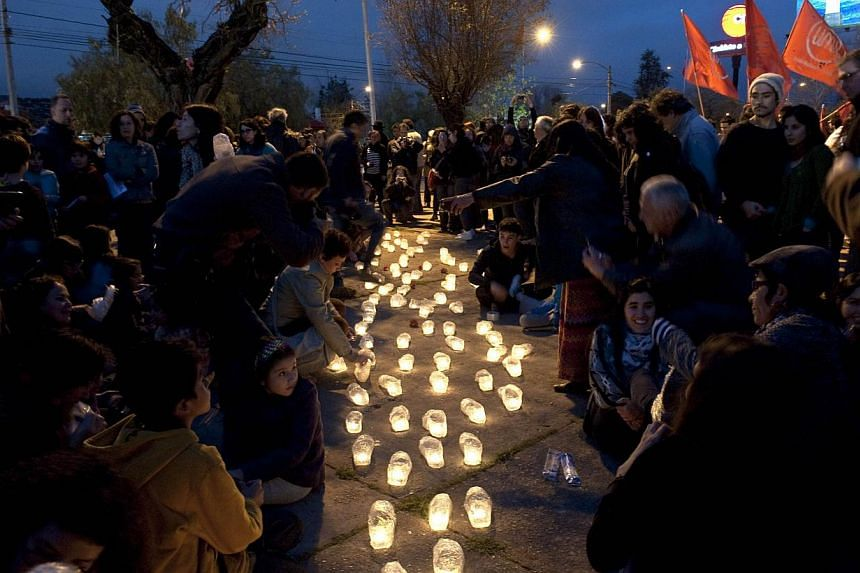 People light candles at the gates of the National Stadium, on Sept 11, 2013 in Santiago, Chile, during the commemoration of the 40th anniversary of the military coup led by General Augusto Pinochet that deposed President Salvador Allende. -- PHOTO: A