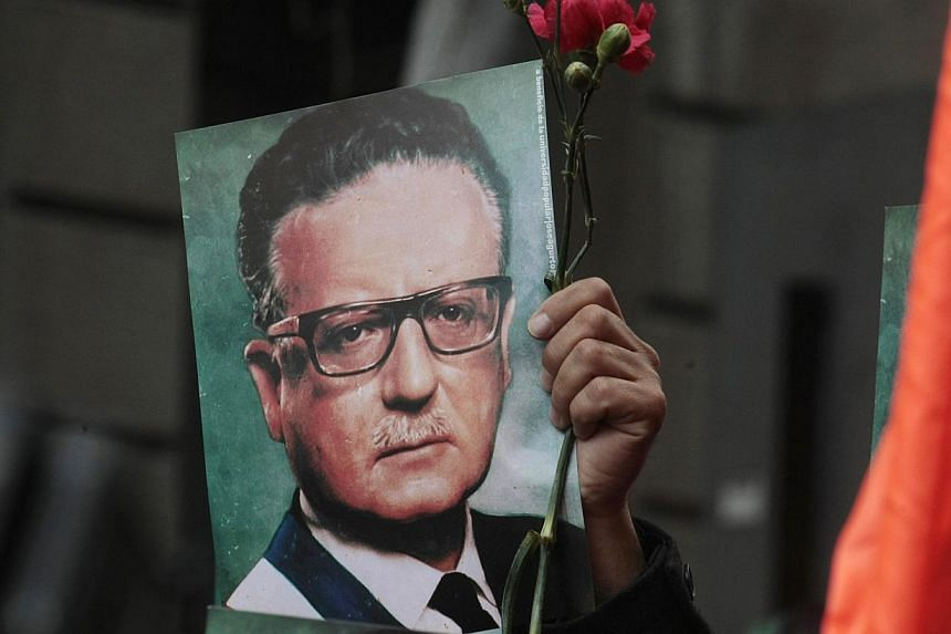 A man holds a photograph of Chile's late President Salvador Allende outside La Moneda presidential palace in Santiago, Chile, Wednesday, Sept 11, 2013. Chile is marking the 40th anniversary of the military coup by General Augusto Pinochet that overth