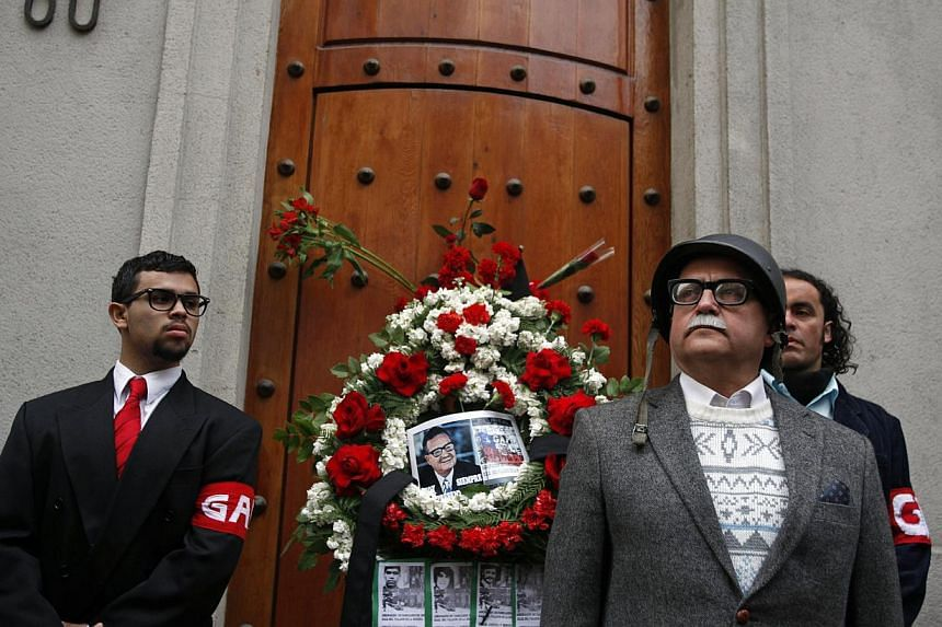 A man dressed in the likeness of Chile's late President Salvador Allende, front right, attends a tribute to Allende on the 40th anniversary of the coup that overthrew him, outside a side door of La Moneda presidential palace in Santiago, Chile, Wedne