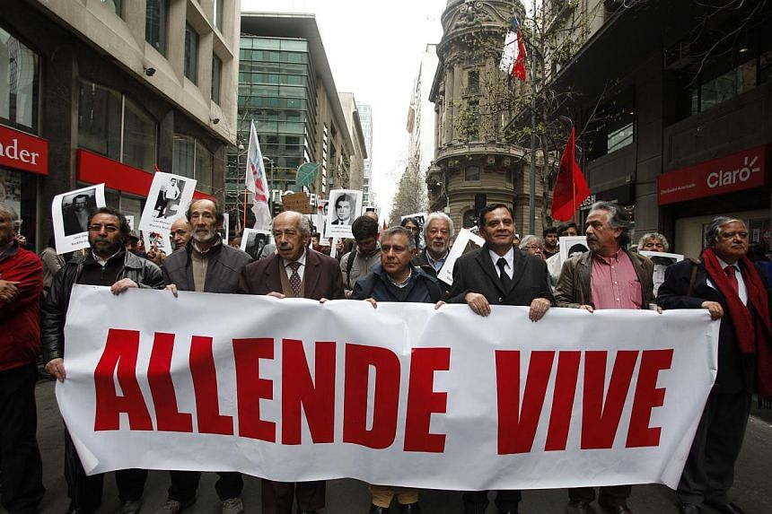 """The relatives of victims of Chile's dictatorship carry a sign that reads in Spanish """"Allende lives"""" referring to Chile's late President Salvador Allende as they march outside La Moneda presidential palace in Santiago, Chile, Wednesday, Sept. 11, 2013"""