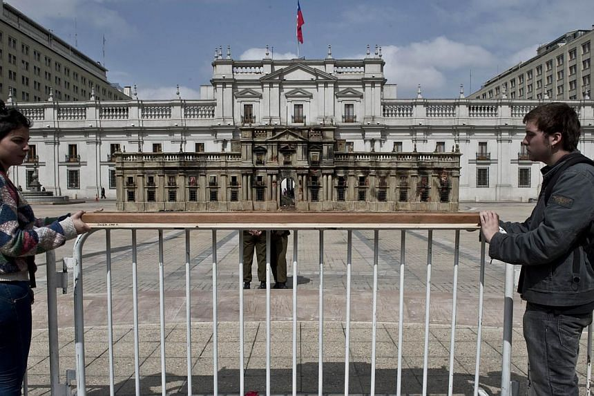 Chilean students hold a scale model of the presidential palace as it looked after the airstrike carried out by the rebellious forces of General Augusto Pinochet that deposed President Salvador Allende, in front of La Moneda Presidential palace in San