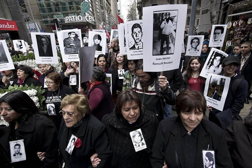 "Activists from Chilean Human Rights organisation ""Detained and Disappeared People"" rally outside La Moneda presidential palace in Santiago, on Sept 11, 2013, during the commemoration of the 40th anniversary of the military coup led by General Augusto"