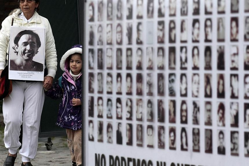 A woman wears a photograph of a victim of the military dictatorship of Gen Augusto Pinochet as she arrives for a ceremony at the Villa Grimaldi detention centre marking the 40th anniversary of the 1973 coup in Santiago, Chile, Tuesday, Sept 10, 2013.
