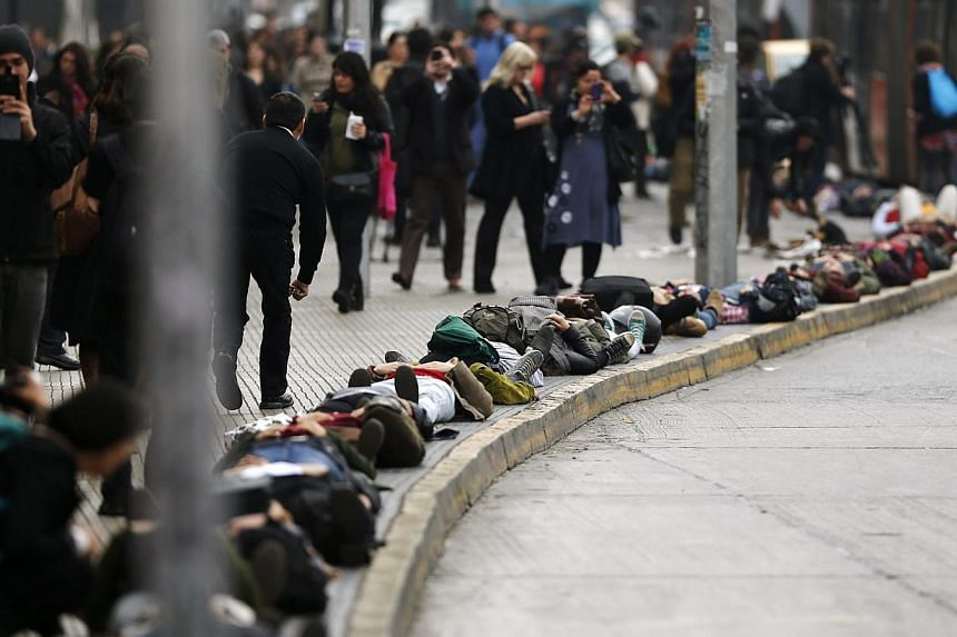Demonstrators lie on the ground to represent people who disappeared and went missing during Augusto Pinochet's regime, during a peaceful protest marking the 40th anniversary of the coup d'etat that ushered in a 17-year dictatorship under Pinochet, in