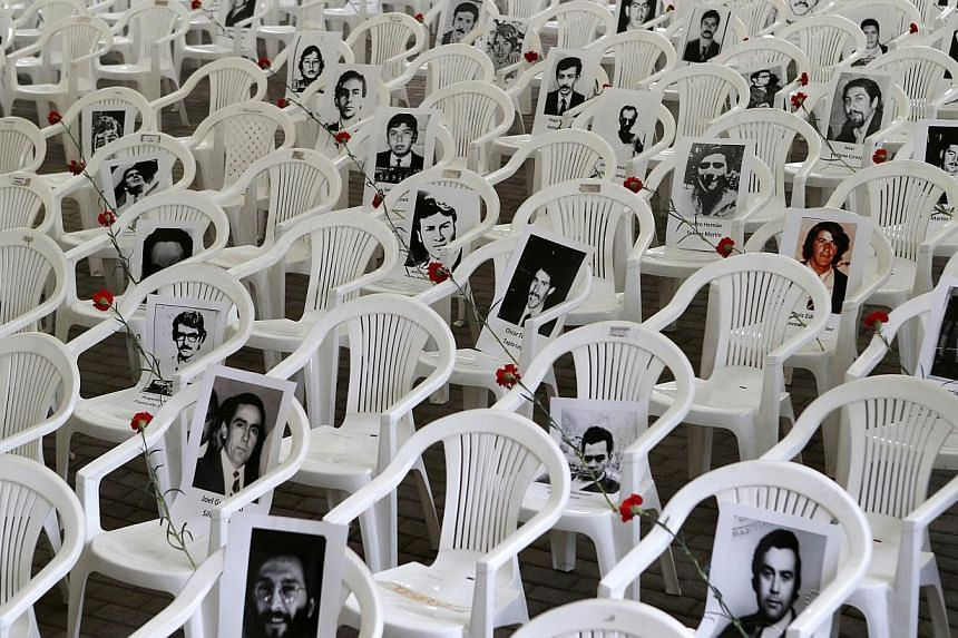 """Pictures of victims of human rights abuse are displayed before a ceremony to commemorate 40 years of the military coup at the """"Parque Por La Paz"""" (Park for Peace) on the grounds of the former Villa Grimaldi torture centre in Santiago, Sept 10, 2013."""