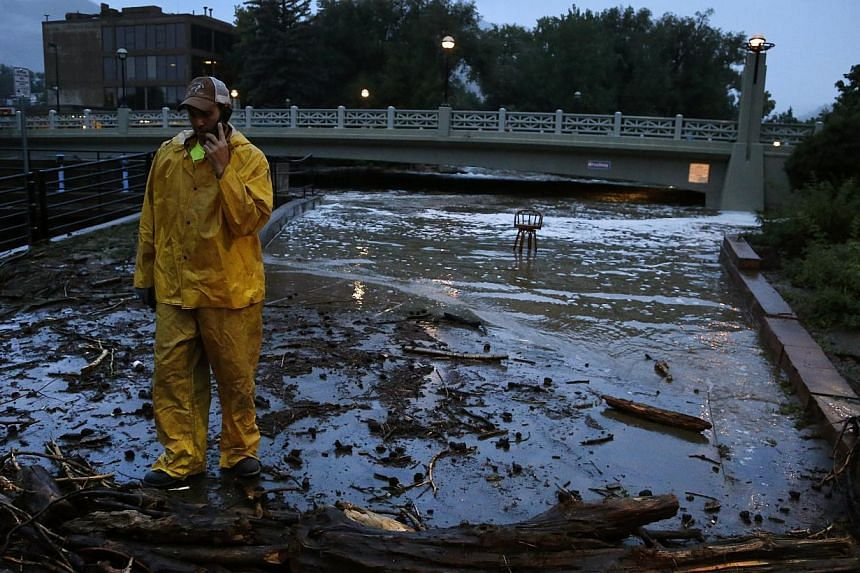 A city worker talks on his phone while surveying high water levels on Boulder Creek following overnight flash flooding in downtown Boulder, Colorado, Thursday, Sept 12, 2013. -- PHOTO: AP