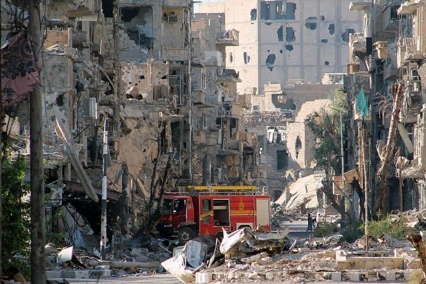 "A picture shows a firetruck left amid heavily damaged buildings in the Syria's eastern town of Deir Ezzor on Tuesday, Sept 10, 2013. A report by United Nations inspectors probing a chemical weapons attack in Syria will ""probably"" be published on"