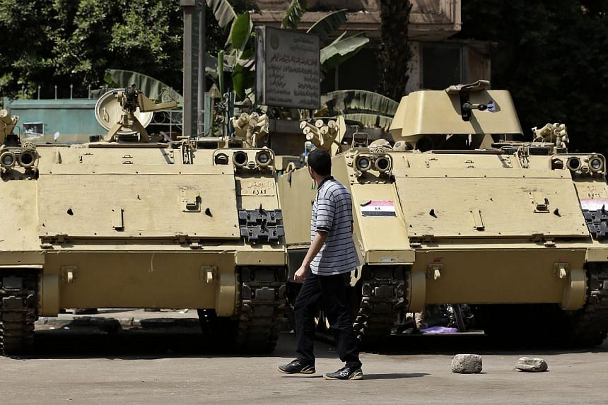 An Egyptian man walks next to armoured personnel carriers on a street in Cairo, Egypt on Thursday, Sept 12, 2013. Interim president Adly Mansour on Thursday extended by two months Egypt's state of emergency in force since mid-August, his spokesm