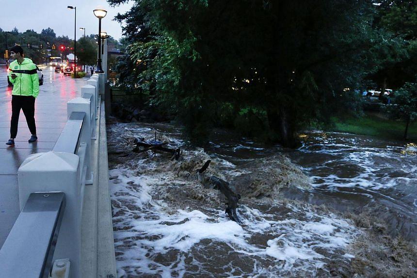 A man walks past dangerously high Boulder Creek following overnight flash flooding in downtown Boulder, Colorado, Thursday, Sept 12, 2013. -- PHOTO: AP