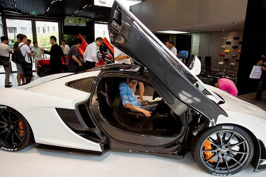 A man is seen sitting inside a car in Mclaren Automotive's first Chinese dealership unveiled on Thursday, Sept 12, 2013, in Shanghai. Britain's McLaren opened its first car dealership in mainland China on Thursday, hoping to sell the country's w