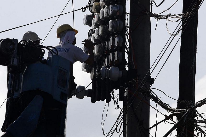 Manila Electric company workers check electric meters in Tondo, Manila, Aug 30, 2013. Unilever Thailand and the Manila Electric Company have won top honours for strong human capital development practices. -- FILE PHOTO: REUTERS
