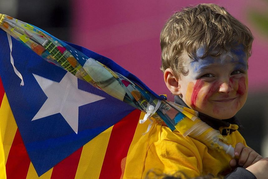 A young boy holding an Independentist Catala flag (Senyera) smiles as Catalans gather in a bid to create a 400km human chain, part of a campaign for independence from Spain during Catalonia National Day, or Diada, outside the FC Barcelona's Camp Nou