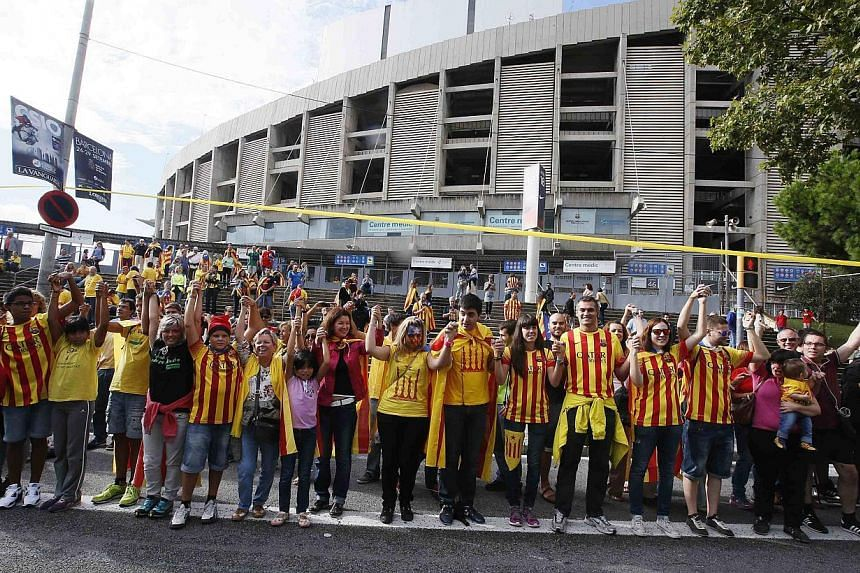 """Catalan separatists form a human chain to mark the """"Diada de Catalunya"""" (Catalunya's National Day) in front of the Nou Camp stadium in Barcelona Sept 11, 2013. Hundreds of thousands of Catalans held hands in a 400km human chain across their region on"""