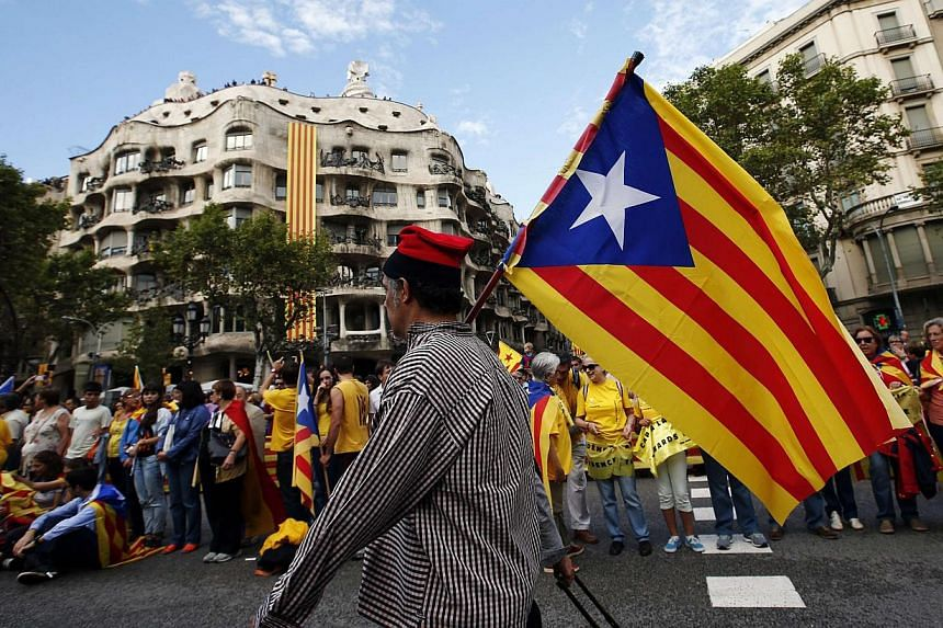 """A man with a pro-independence Catalan flag walks in front of people forming a human chain to mark the """"Diada de Catalunya"""" (Catalunya's National Day) in central Barcelona Sept 11, 2013. Hundreds of thousands of Catalans held hands in a 400km human ch"""
