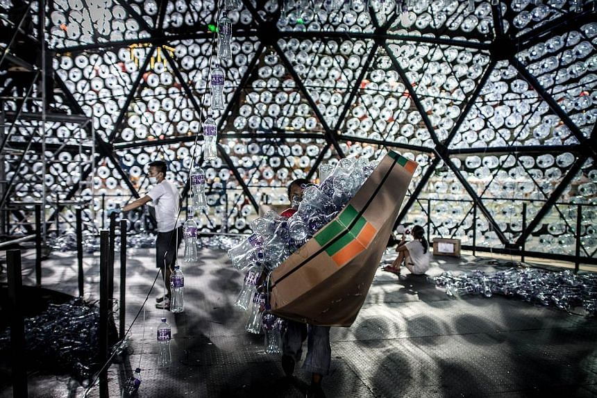 A worker carrying a box of plastic bottles to be part of a three-storey high lantern made of recycled plastic bottles on Sept 12, 2013, in Hong Kong.