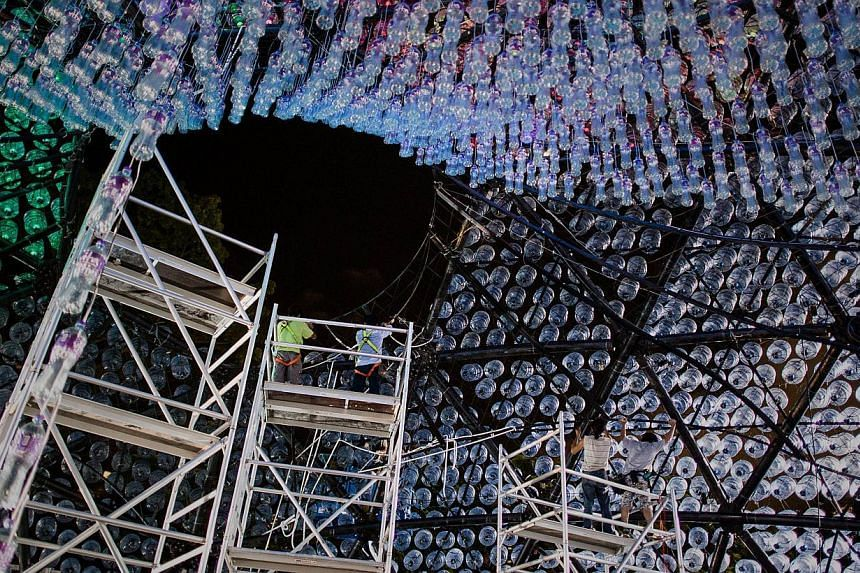 Workers sort out electric cables inside a three-storey high lantern made of recycled plastic bottles on Sept 12, 2013, in Hong Kong. -- PHOTO: AFP