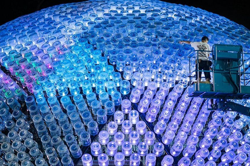 Workers sort out electric cables on a three-storey high lantern made of recycled plastic bottles on Sept 12, 2013, in Hong Kong. -- PHOTO: AFP