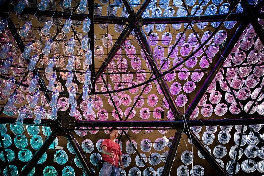 A worker sorts out the electric cables of a three-storey high lantern made of recycled plastic bottles on Sept 12, 2013, in Hong Kong. -- PHOTO: AFP