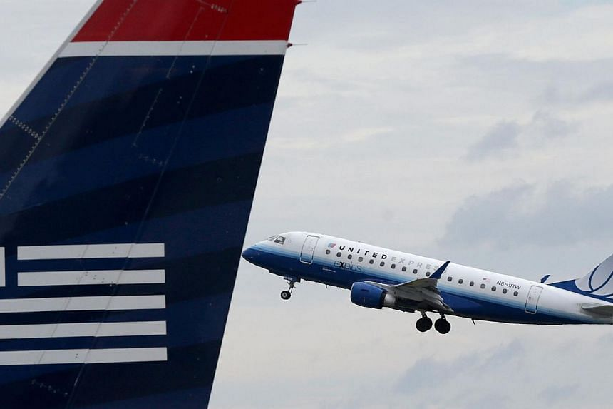 A United Airlines jet takes off behind a US Airways jet at Ronald Reagan Washington National Airport on Aug 13, 2013 in Arlington, Virginia. An unknown number of United Airlines customers purchased US flight tickets for practically nothing for a shor