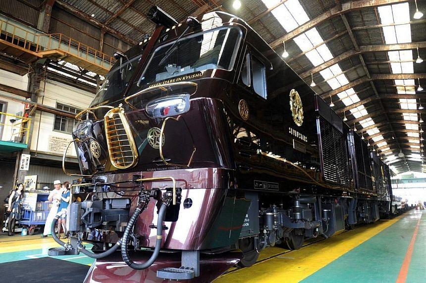 "Japan's Kyushu railway unveils a new super-luxury train ""Nanatsuboshi"" - Seven Stars - at the company's train yard in Kitakyushu in Fukuoka prefecture, Japan's southern island of Kyushu on Friday, Sept 13, 2013.A Japanese railway operator on Fr"