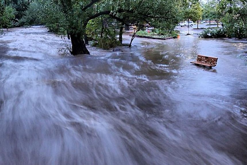 In this image made with a slow shutter speed which blurred the rushing water, flood waters course through a small park in Boulder, Colorado, on Sept 12, 2013. Rare torrential downpours unleashed flash flooding in Colorado that killed at least three p