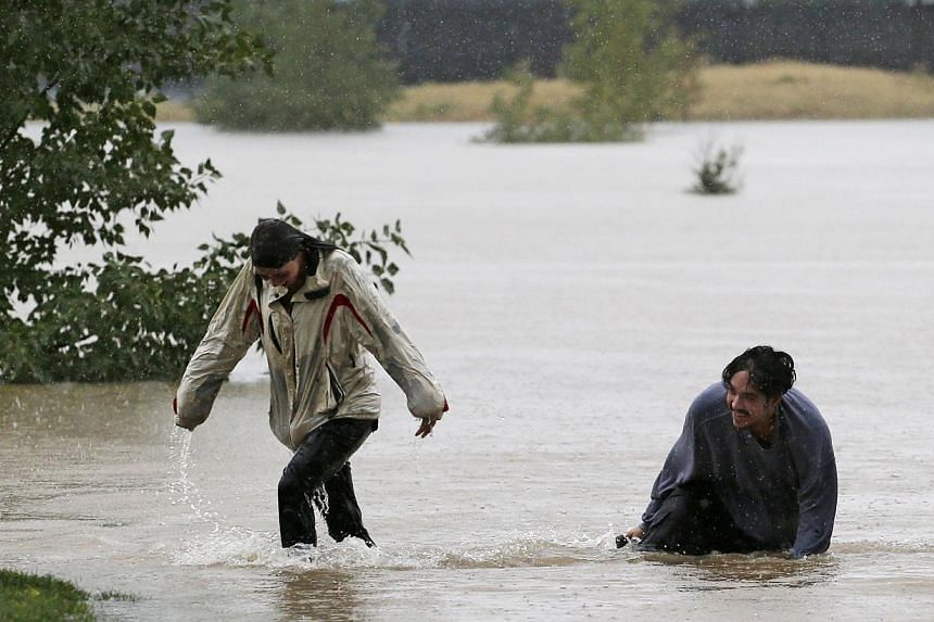 A couple plays in flood water at Utah Park in Aurora, Colorado, on Sept 12, 2013. Rare torrential downpours unleashed flash flooding in Colorado that killed at least three people, left one missing and forced thousands to flee to higher ground on Thur