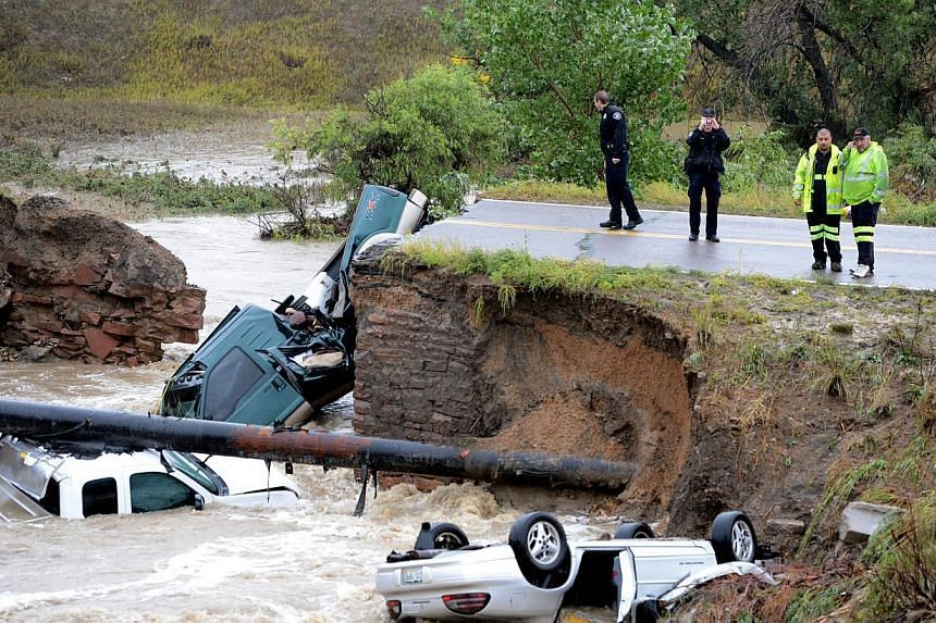 A bridge collapses on a business access road at Highway 287 and Dillon Road at the Broomfield/Lafayette border, Colorado, after flash flooding caused three cars to fall in the creek on Sept 12, 2013. Rare torrential downpours unleashed flash flooding