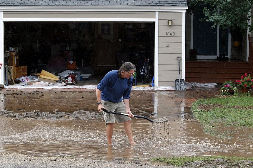 Mr Brian Flynn of Oregon clears a drain in front of his sister's home in Boulder, Colorado, on Sept 12, 2013. Flash flooding in Colorado has cut off access to towns, closed the University of Colorado in Boulder and left at least three people dead.--