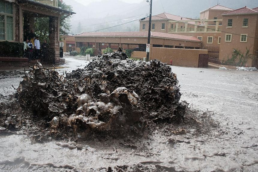Flood water shoots out of a sewer on Canon Avenue on Sept 12, 2013, in Manitou Springs, Colorado. Flash flooding in Colorado has cut off access to towns, closed the University of Colorado in Boulder and left at least three people dead. -- PHOTO: AP