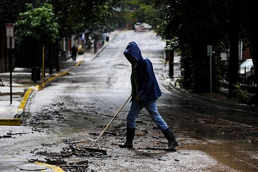 A man begins cleaning up Canon Avenue in Manitou Springs, Colorado, after a flash flood burst through a manhole and sent water rushing down the streets on Sept 12, 2013. Rare torrential downpours unleashed flash flooding in Colorado that killed at le