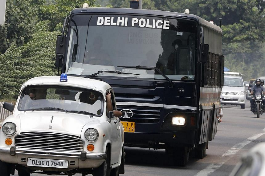 A police bus carrying four men who were found guilty of the fatal gang-rape of a young woman on a bus, arrives at a court in New Delhi on Friday, Sept 13, 2013. The judge hearing the case of four men sentenced them to death on Friday.-- PHOTO: