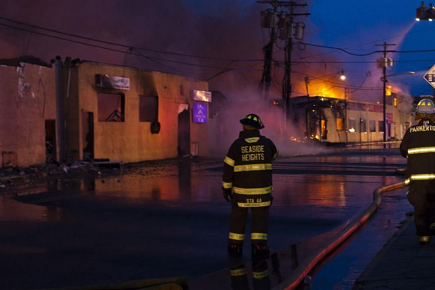 New Jersey firefighters work near smoke rising from a massive fire in Seaside Park in New Jersey on Sept 12, 2013. The fire engulfed several blocks of boardwalk and businesses on Thursday in Seaside Park, a shore town that was still rebuilding from d