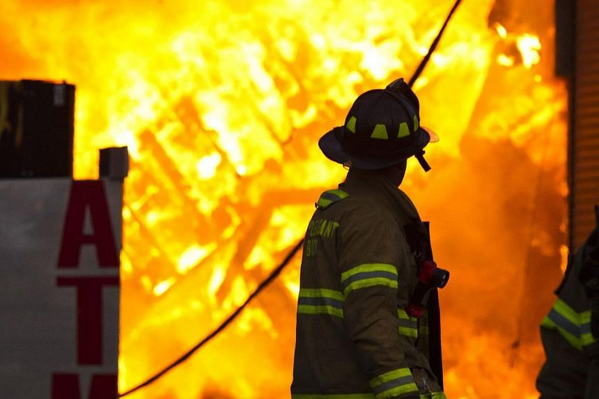 A New Jersey firefighter walks near a store in flames during a massive fire in Seaside Park in New Jersey on Sept 12, 2013. The fire engulfed several blocks of boardwalk and businesses on Thursday in Seaside Park, a shore town that was still rebuildi