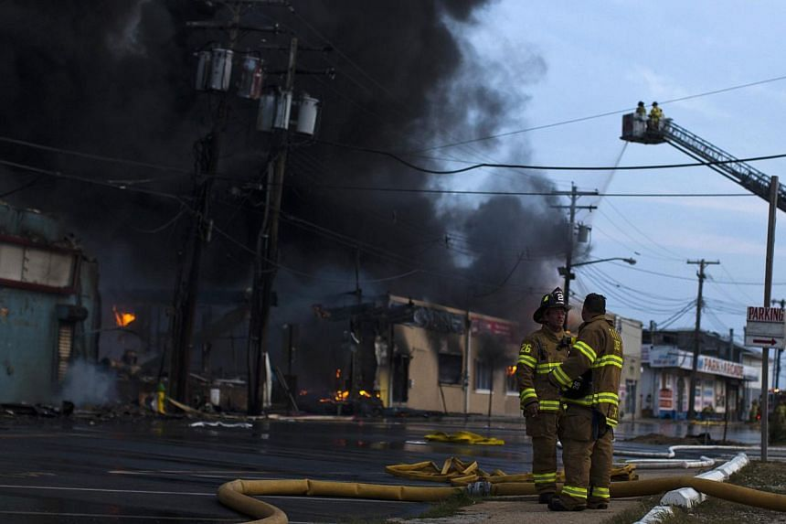 New Jersey firefighters stand near smoke rising from a massive fire in Seaside Park in New Jersey on Sept 12, 2013. The fire engulfed several blocks of boardwalk and businesses on Thursday in Seaside Park, a shore town that was still rebuilding from