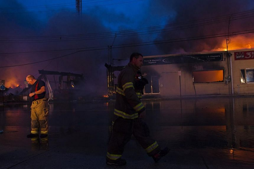 New Jersey firefighters walk near a burning store during a massive fire in Seaside Park in New Jersey on Sept 12, 2013. The fire engulfed several blocks of boardwalk and businesses on Thursday in Seaside Park, a shore town that was still rebuilding f