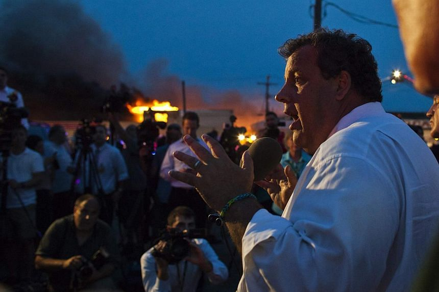New Jersey Governor Chris Christie (right) speaks with the media while firefighters work to control a massive fire in Seaside Park in New Jersey on Sept 12, 2013. The fire engulfed several blocks of boardwalk and businesses on Thursday in Seaside Par