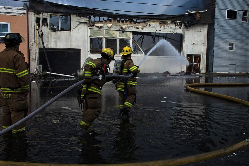 New Jersey firefighters spray water as they work to control a fire in Seaside Park in New Jersey on Sept 12, 2013. The fire engulfed several blocks of boardwalk and businesses on Thursday in Seaside Park, a shore town that was still rebuilding from d