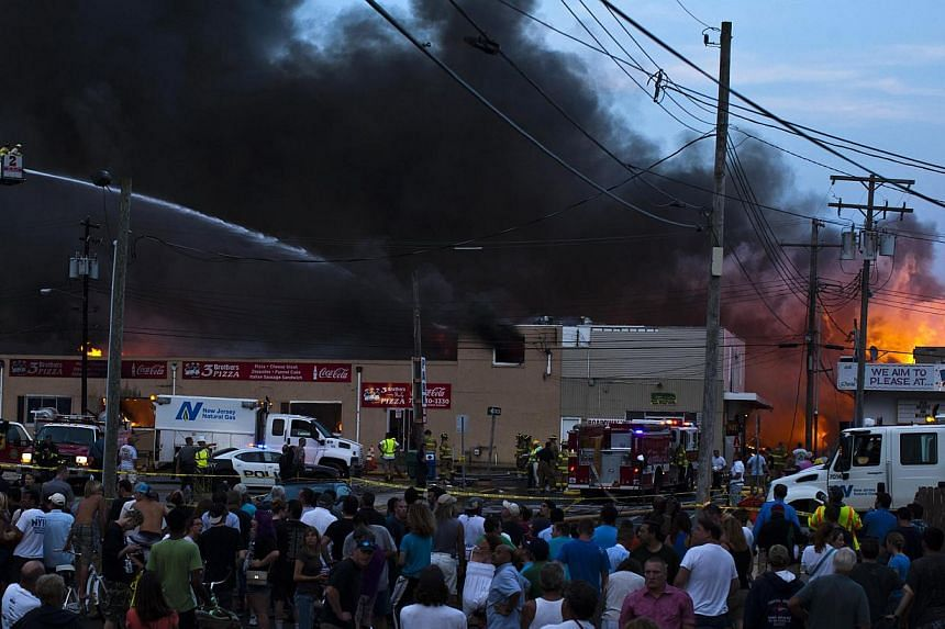 Residents look at New Jersey firefighters working to control a massive fire in Seaside Park in New Jersey on Sept 12, 2013. The fire engulfed several blocks of boardwalk and businesses on Thursday in Seaside Park, a shore town that was still rebuildi